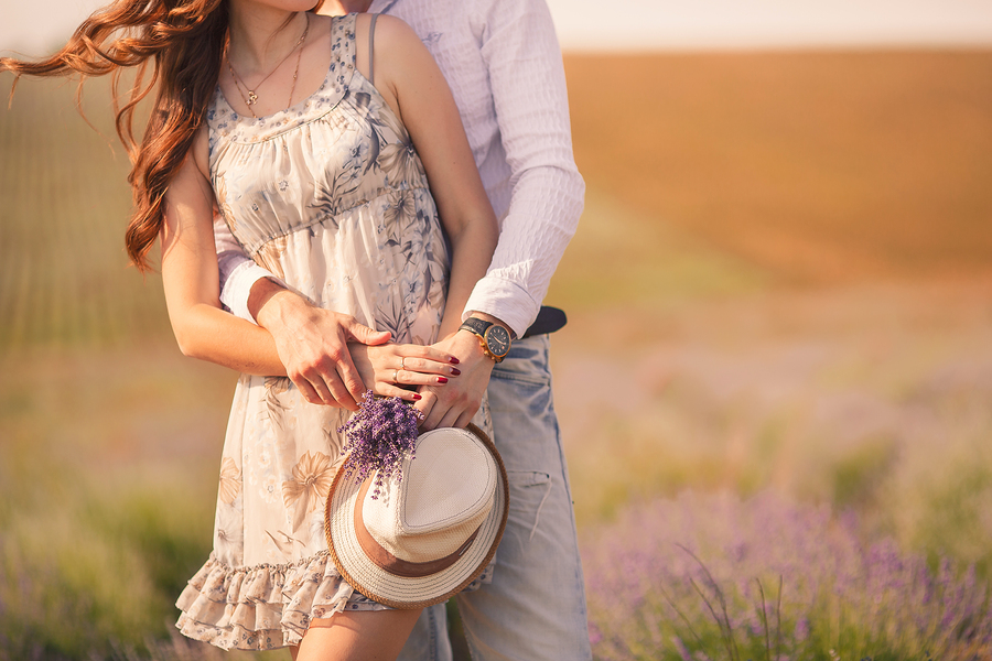Young beautiful sensual couple kissing outdoors in windy weather in the summer on a lavender field.