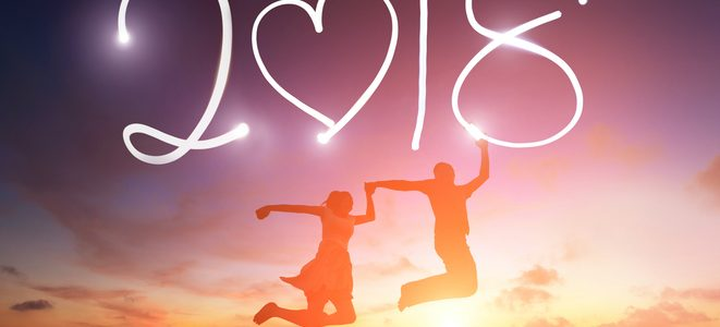 silhouette of young couple jumping and drawing 2018 new year by digital tablet pc flashlight in the air on beach